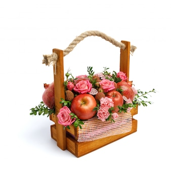 Unikalne drewniane pudełko z kwiatami i owocami na białym tle. widok z lewej strony