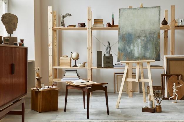 Unikalne wnętrze miejsca pracy artysty ze stylową komodą z drewna tekowego, drewnianą sztalugą, regałem, dziełami sztuki, akcesoriami malarskimi, dekoracjami i eleganckimi rzeczami osobistymi. nowoczesna pracownia dla artysty.