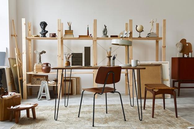 Unikalne wnętrze miejsca pracy artysty ze stylowym biurkiem, drewnianą sztalugą, regałem, dziełami sztuki, akcesoriami malarskimi, dekoracjami i eleganckimi rzeczami osobistymi. nowoczesna pracownia dla artysty.