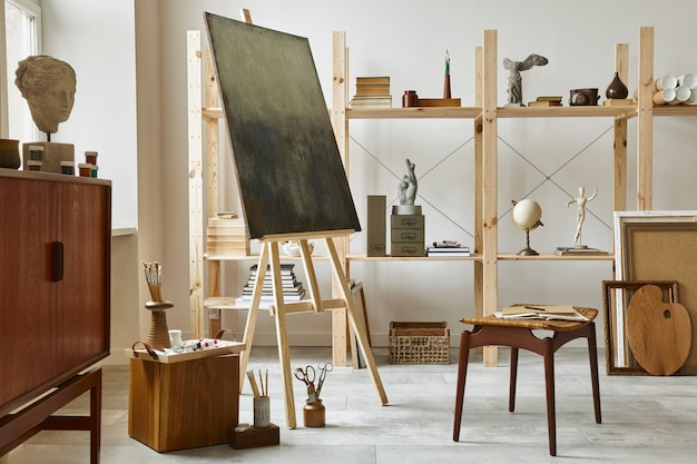 Unikalne wnętrze pracowni artysty ze stylową komodą z drewna tekowego, drewnianą sztalugą, regałem, dziełami sztuki, akcesoriami malarskimi, dekoracjami i eleganckimi rzeczami osobistymi. nowoczesna pracownia artystyczna..