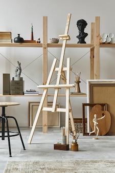 Unikalne wnętrze pracowni artysty ze stylową komodą z drewna tekowego, drewnianą sztalugą, regałem, dziełami sztuki, akcesoriami malarskimi, dekoracjami i eleganckimi rzeczami osobistymi. nowoczesna pracownia artystyczna.