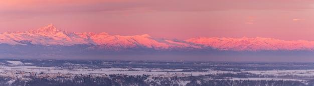 Unikalny krajobraz pokrytego śniegiem pasma górskiego na dużych wysokościach w piemoncie we włoszech. szczyt górski mon viso. epickie światło wschodu słońca w zimie, dramatyczne niebo.