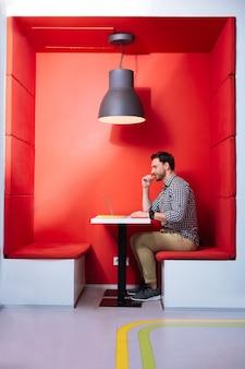 Uniwersytet futurystyczny. spokojny, uważny student siedzący w wygodnej, futurystycznej, czerwonej przestrzeni i w zamyśleniu spoglądający na ekran nowoczesnego laptopa
