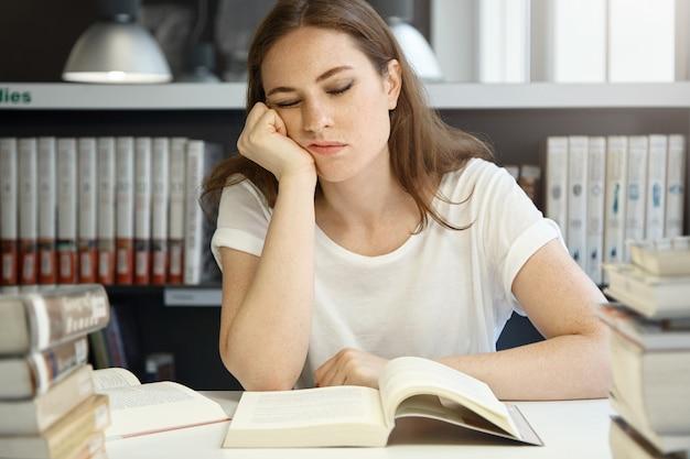 Uniwersytet medyczny kaukaska studentka studiuje w bibliotece, piękna kobieta kolegium śpi siedząc przed otwartą książką opierając brodę na dłoni, wyglądając na wyczerpanego.