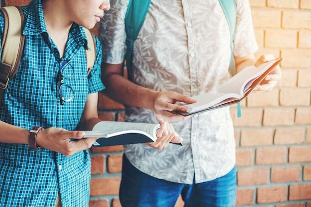 Uniwersytet studiuje przyjaciół studiujących i czytających książki w klasie