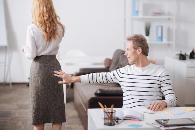 Unmannered uśmiechnięty dojrzały kierownik biura siedzi w biurze i pracuje, dotykając ciała kolegów