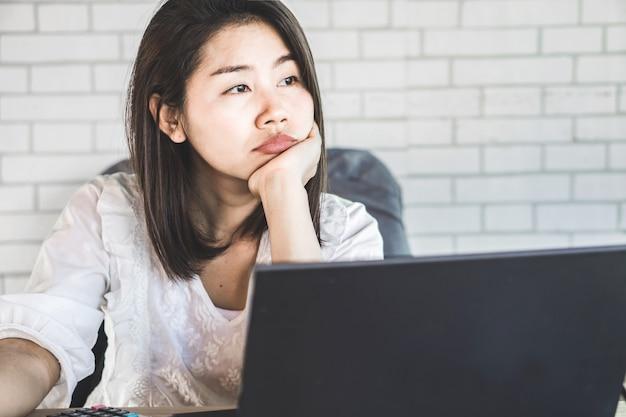 Unmotivated azjatycki żeński pracownik siedzi przy biurkiem