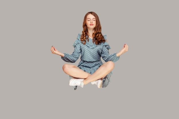 Unosić się w powietrzu. spokojna, spokojna, zrelaksowana dziewczyna lewitująca gestem mudry z rękami w górze,