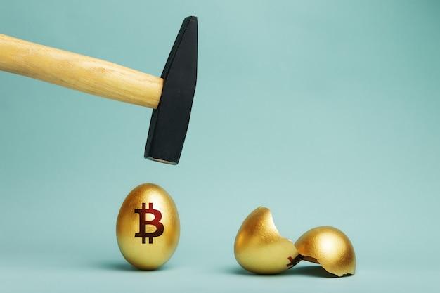 Unoszące się nad nim złote jajko bitcoin i młotek przed uderzeniem złamane jajko bitcoin. upadek bitcoinów, koncepcja utraty pieniędzy.