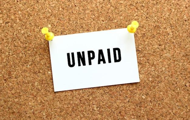 Unpaid jest napisane na karcie przyczepionej do tablicy korkowej za pomocą przycisku. przypomnienie na tablicy biurowej. pomysł na biznes.