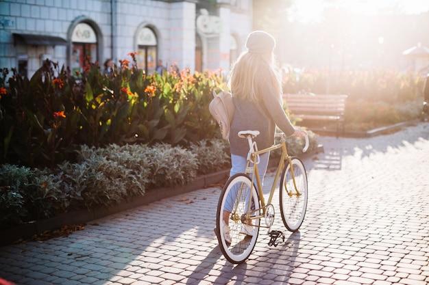 Unrecognizable kobiety odprowadzenie z bicyklem w parku