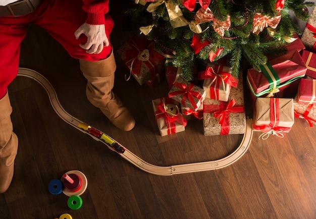 Unrecognizable święty mikołaj bawić się z drewnianą linią kolejową blisko choinki