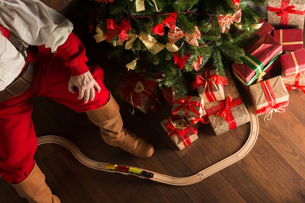 Unrecognizable święty Mikołaj Bawić Się Z Drewnianą Linią Kolejową Blisko Choinki Premium Zdjęcia