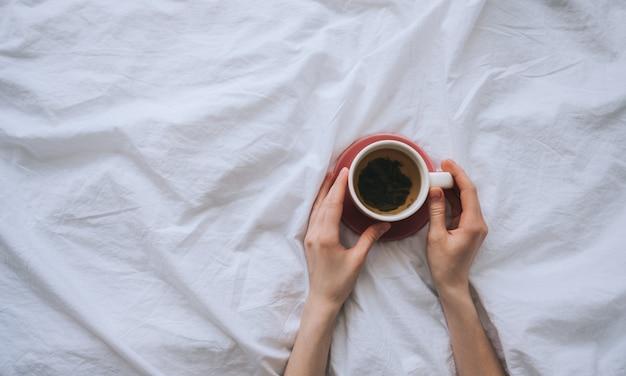 Up z herbatą w dłoni na białym łóżku z miejscem na kopię. leżał płasko