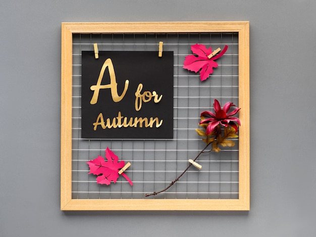 """Upadek koncepcji rzemiosła z papieru do projektowania wnętrz lub kreatywnych pomysłów na dekorację wnętrz. tablica fotograficzna z fioletowym papierem jesienne liście, kwiat i papierowy tekst """"a na jesień""""."""