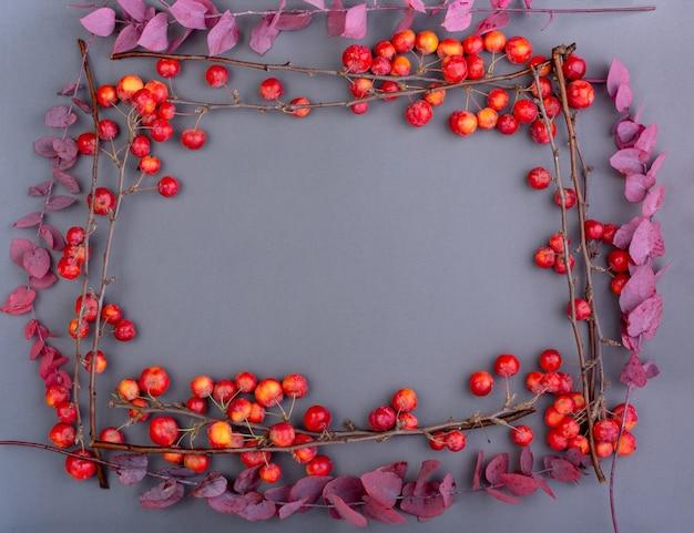 Upadek płaskich czerwonych jabłek i zwiędłych jesiennych liści na szaro