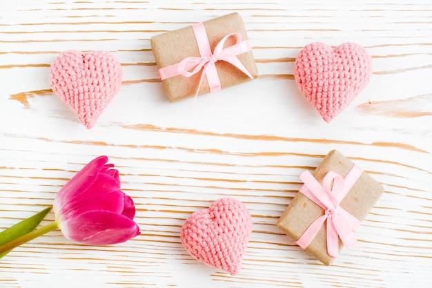Upakowane prezenty z różową wstążką, dzianiny serca i tulipan na białym drewnie, widok z góry