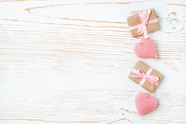 Upakowane prezenty z różową wstążką i dzianiny serca na białym drewnie, widok z góry