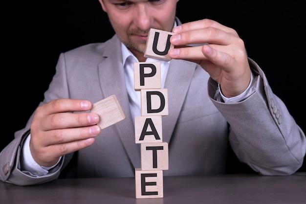 Update, słowo napisane jest na drewnianych kostkach, klocki na tle mężczyzny, biznesmena w szarym garniturze.
