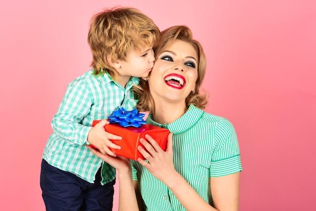 Upiąć kobietę z małym chłopcem. syn całuje matkę. dzień matki. pin up kobieta w zielonej sukni posiada pudełko. mały chłopiec w zielonej koszuli. na białym tle na różowym tle. rodzina. relacje rodzinne.