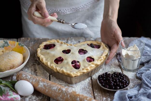 Upiec ciasto owocowe w kształcie. cukier posypany plackiem owocowym.