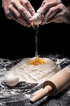 Upiecz to. zbliżenie na ręce szefa kuchni mans przygotowując ciasto i używając jaj i mąki podczas pracy w restauracji.
