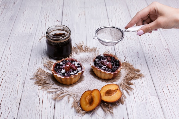 Upieczone kosze z jagodami, słodką śmietaną i miodem