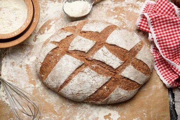 Upieczony bochenek chleba na stole i składniki, naczynia kuchenne leżą w pobliżu, widok z góry