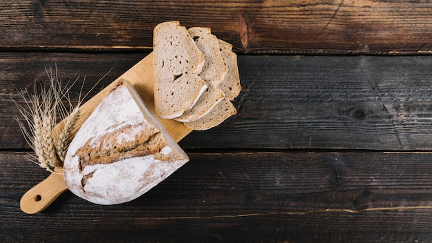 Upieczony chleb i kłos pszenicy na desce do krojenia na drewnianym stole