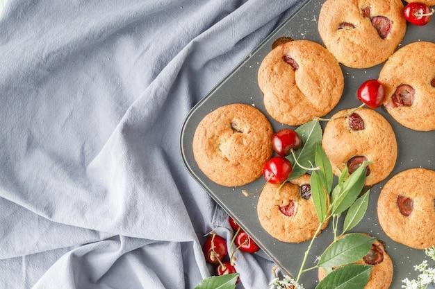 Upieczony muffin wiśniowy na tacy muffinowej
