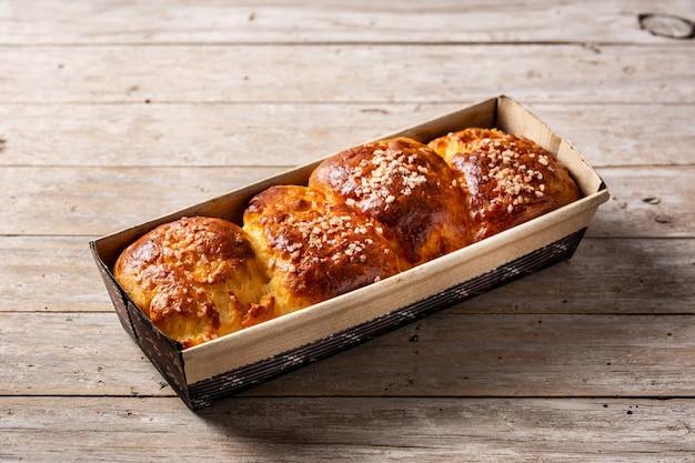 Upieczony pleciony chleb brioche na drewnianym stole