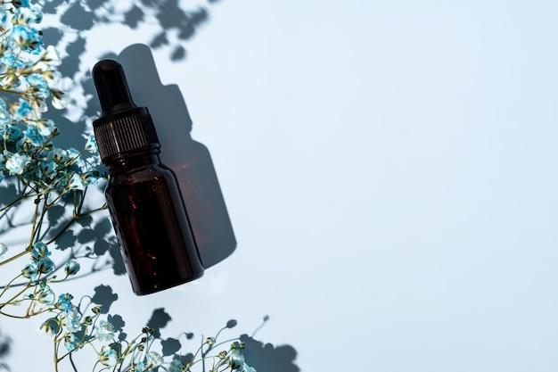 Upiększający olejek lub serum do twarzy z naturalnymi składnikami na niebieskim tle z kwiatami. koncepcja leczenia pielęgnacji skóry. niemarkowy pakiet do projektowania z miejscem na kopię
