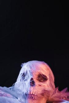 Upiorna czaszka w plastikowym materiale oświetlona fioletowym światłem