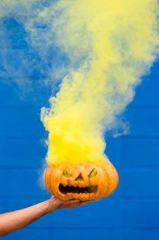 Upiorna dynia halloweenowa z żółtym dymem