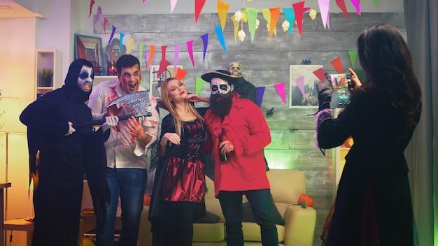 Upiorna wiedźma robiąca zdjęcia swoim przerażającym przyjaciołom podczas świętowania halloween w udekorowanym domu