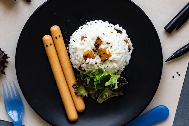 Upiorne jedzenie dla dzieci na halloween z ryżem dyniowym i parówkami