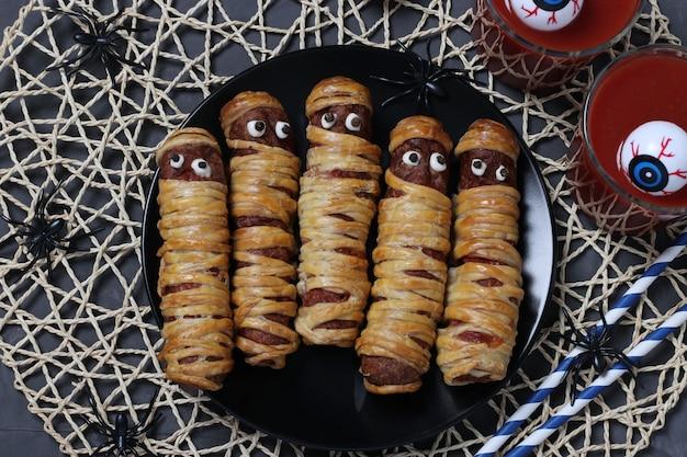 Upiorne mumie kiełbasiane i sok pomidorowy na halloween na ciemnym talerzu, leżał na płasko. widok z góry