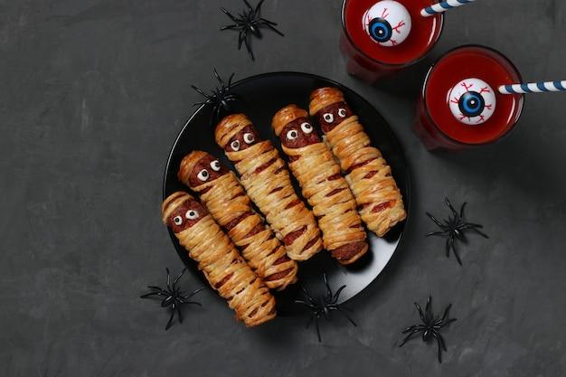 Upiorne mumie kiełbasy i sok pomidorowy na imprezę halloween na ciemnym talerzu, widok z góry. leżał płasko. format poziomy.