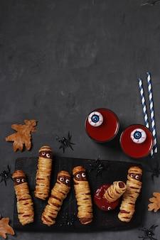 Upiorne mumie kiełbasy, sok pomidorowy i sos na halloween na ciemnej drewnianej desce. widok z góry. leżał płasko. format pionowy. skopiuj miejsce.
