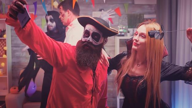 Upiorne postacie piratów i krwawych wiedźm robią sobie selfie na imprezie halloweenowej, podczas gdy ich przyjaciele tańczą i bawią się w udekorowanym domu