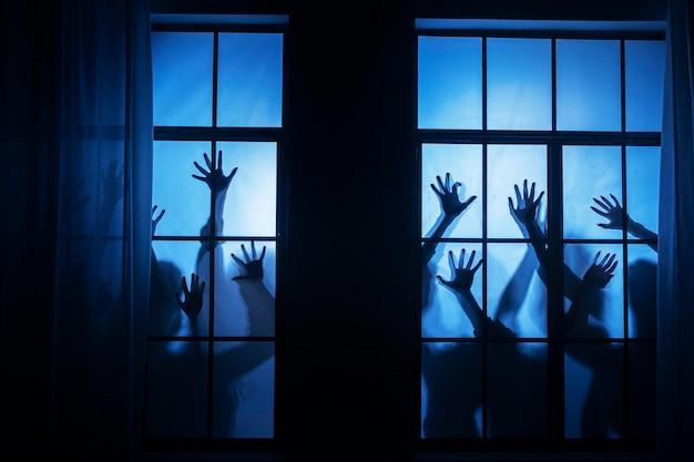 Upiorne ręce zombie na oknie