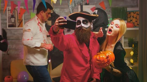 Upiorny brodaty pirat robi selfie z piękną kobietą reperującą na imprezie halloweenowej, podczas gdy inni tańczą w udekorowanym domu