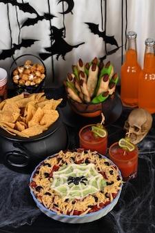 Upiorny halloweenowy siedmiowarstwowy dip taco: zamień klasyczną przystawkę w halloween z czarnym oliwkowym pająkiem.