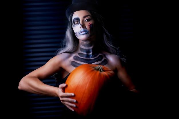 Upiorny portret kobiety w halloweenowym gotyckim makijażu trzyma dynię