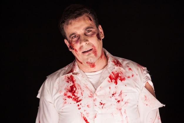 Upiorny zombie z krwawymi bliznami na twarzy na czarnym tle. zły człowiek.