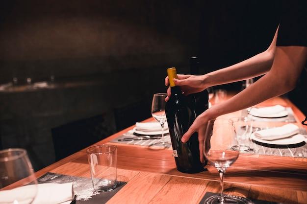Upraw gospodyni stawiając wino na stole