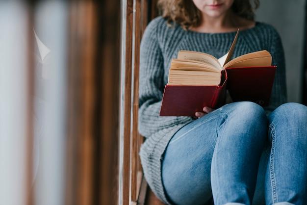 Upraw kobieta cieszy się czytać blisko okno