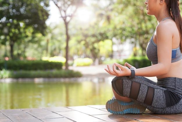 Upraw kobieta medytuje w zielonym lato parku