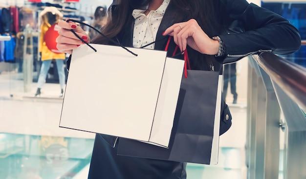 Upraw krótki kobieta patrząc na białą torbę na zakupy na tle centrum handlowego. pani stojąca w centrum handlowym przy balustradzie i otwierająca paczkę z zakupami. bliska kobiece ręce patrząc wewnątrz torby.