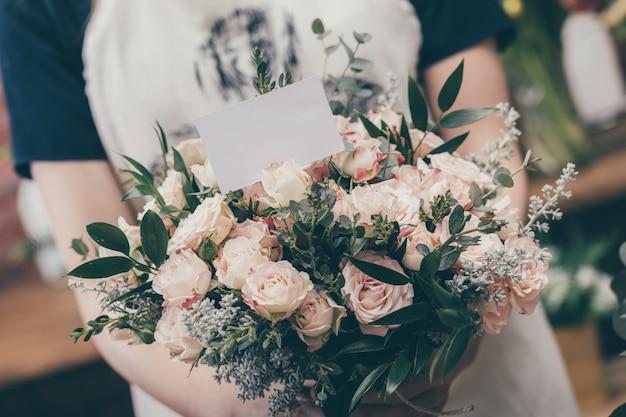 Upraw kwiaciarnia pokazuje bukiet z pocztówką